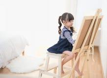 Cute little girl drawing on chalkboard Stock Photo