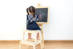 Cute little girl drawing on chalkboard Stock Photography
