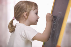 Cute Little Girl Drawing On Chalkboard Royalty Free Stock Image