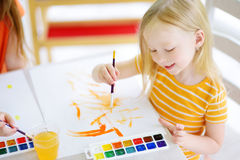 Cute little girl drawing with colorful paints at a daycare. Creative kid painting at school. Girl doing homework at home stock photography