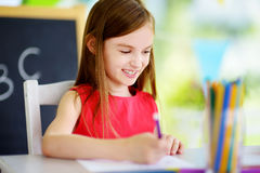 Cute little girl drawing with colorful pencils at a daycare. Creative kid painting at school Royalty Free Stock Photo