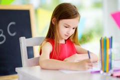 Cute little girl drawing with colorful pencils at a daycare. Creative kid painting at school Stock Photography