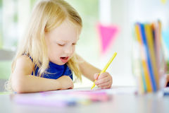 Cute little girl drawing with colorful pencils at a daycare. Creative kid painting at school Royalty Free Stock Photography