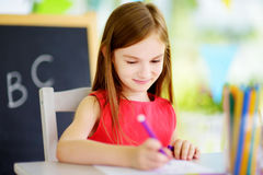 Cute little girl drawing with colorful pencils at a daycare. Creative kid painting at school Stock Images