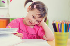 Cute little girl drawing with colorful pencils Royalty Free Stock Image