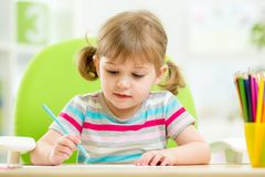 Cute little girl drawing with colourful pencils Stock Photography