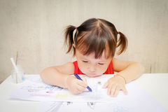 Cute little girl is drawing with crayon in preschool ,unlimited boundless imagination through Colorful :children. Development concept royalty free stock photos