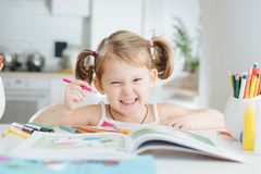 Cute little girl is drawing with felt-tip pen at home. Cute little girl with two tails is drawing in coloring book with colored pencil at home. Angry grin royalty free stock photo