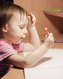 Cute little girl is drawing with felt-tip pen Stock Images
