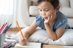Cute little girl drawing homework and writing with pen on paper in her home. At happiness royalty free stock image