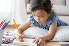 Cute little girl drawing homework and writing with pen on paper in her home. Strict face royalty free stock images
