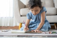 Cute little girl drawing homework and writing with pen on paper in her home. Cute little girl drawing homework and writing with pen on paper in living room her royalty free stock photo