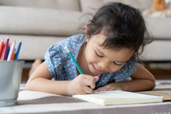 Cute little girl drawing homework and writing with pen on paper in her home. Happily royalty free stock photo