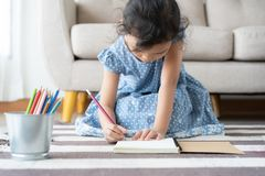 Cute little girl drawing homework and writing with pen on paper in her home. Cute little girl drawing homework and writing with pen on paper at living room in royalty free stock photography