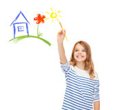 Cute little girl drawing house with brush. Education, school and imaginary screen concept - cute little girl drawing house with brush Stock Images