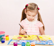Cute little girl drawing with paint and paintbrush Royalty Free Stock Photos