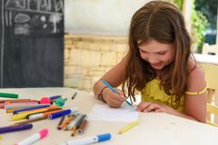 Cute little girl drawing and painting at kindergarten. Creative activities kids club. Cute little girl drawing and painting with chalk at kindergarten. Creative royalty free stock images