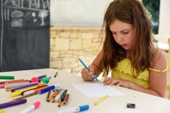 Cute little girl drawing and painting at kindergarten. Creative activities kids club stock photo