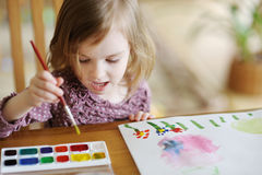 Cute little girl is drawing with paints Royalty Free Stock Photography