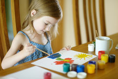 Cute little girl is drawing with paints. In preschool stock photography