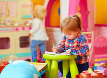 Cute little girl drawing with pencil in kindergarten Royalty Free Stock Image