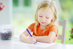 Cute little girl drawing with pencils at a daycare. Creative kid painting at school. Girl doing homework at home. Royalty Free Stock Images