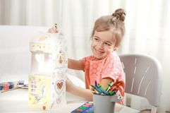 Cute little girl drawing with pencils at home. A cute little girl is painting a paper house with colored pencils in a homely atmosphere. The concept of child royalty free stock image