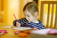 Cute little girl is drawing with pencils Royalty Free Stock Images