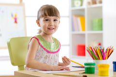 Cute little girl is drawing with pencils in preschool stock image