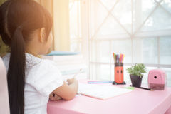 Cute little girl drawing picture using her imagination stock images