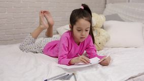 Cute little girl drawing pictures while lying on bed.