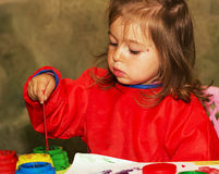 Cute little girl drawing and studying at daycare. Cute little kid drawing and studying at daycare Stock Photos