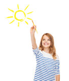 Cute little girl drawing sun with brush. Education, school and imaginary screen concept - cute little girl drawing sun with brush Royalty Free Stock Photo