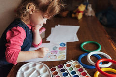 Cute little girl draws a circle of colored paints Royalty Free Stock Photo