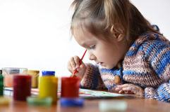 Cute little girl draws paint Stock Images