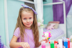Cute Little girl draws paints at her table in the Stock Photo