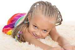 Cute little girl with dreadlocks lays. On the mat. Girl six years royalty free stock photo