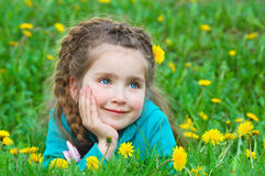 Cute little girl dreaming on green grass Stock Photos