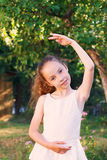 Cute little girl dreams of becoming a ballerina. Child girl in w. Hite dress dancing outside.  Beautiful Girl is studying ballet Royalty Free Stock Image