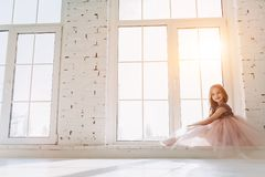 Cute little girl in dress. Cute little girl in beautiful dress is sitting on a window sill at light sunny room Stock Photography