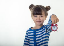 Cute little girl in dress with red alarm clock on white background. royalty free stock photo