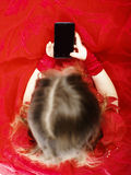 Cute little girl dressed in ball gown playing with smartphone Stock Photos