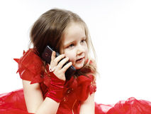 Cute little girl dressed in ball gown playing with smartphone Stock Image
