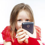 Cute little girl dressed in ball gown playing with smartphone Royalty Free Stock Photo