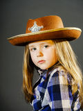 Cute little girl dressed in cowboy shirt and sheriff hat. Isolated studio portrait Royalty Free Stock Images