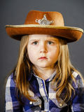 Cute little girl dressed in cowboy shirt and sheriff hat. Isolated studio portrait Stock Photo