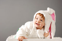 Cute little girl dressed in Easter bunny suit. Over gray background Stock Photo
