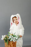 Cute little girl dressed in Easter bunny suit. Portrait of a cute little girl dressed in Easter bunny suit holding spring flower bouquet Royalty Free Stock Photos
