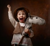 Cute little girl dressed like a cowboy playing with a homemade h. Orse. Expressive facial expressions Stock Photo