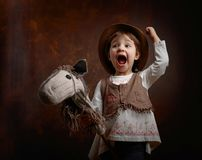 Cute little girl dressed like a cowboy playing with a homemade h. Orse. Expressive facial expressions Royalty Free Stock Photography